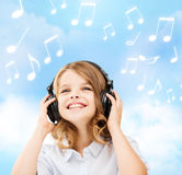 Smiling little girl with headphones at home. Home, leisure, new technology and music concept - smiling little girl with headphones over blue sky background and stock photos