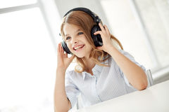 Smiling little girl with headphones at home Stock Photo