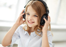 Smiling little girl with headphones at home Stock Images