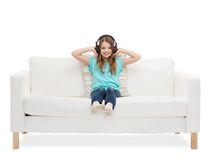 Smiling little girl in headphones sitting on sofa Royalty Free Stock Photos