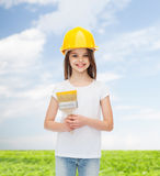 Smiling little girl in helmet with paint brush Royalty Free Stock Image