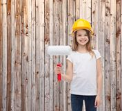 Smiling little girl in helmet with paint roller Royalty Free Stock Image