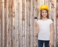 Smiling little girl in helmet with paint roller Stock Images