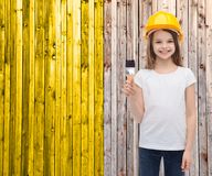 Smiling little girl in helmet with paint roller Royalty Free Stock Photography