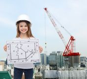 Smiling little girl in helmet showing blueprint Stock Photography