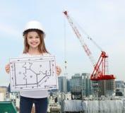 Smiling little girl in helmet showing blueprint stock photography