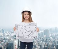 Smiling little girl in helmet showing blueprint Stock Photos