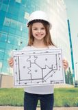 Smiling little girl in helmet showing blueprint Stock Images