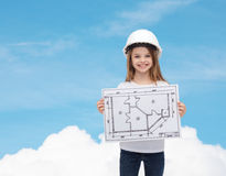 Smiling little girl in helmet showing blueprint Royalty Free Stock Photos