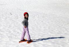 Smiling little girl with helmet and snowshoes on the snow Stock Photos