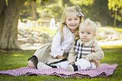 Smiling Little Girl with Her Baby Brother at the Park Royalty Free Stock Image
