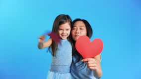Smiling little girl and her mom holding paper heart