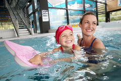 Smiling little girl with her mother in swimming pool Stock Photography