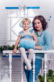 Smiling little girl with her older sister standing next to a Chr Royalty Free Stock Photo
