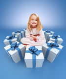 Smiling little girl in her pajamas surrounded by gifts Stock Images