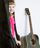 Smiling little girl hiding in a guitar's cover Royalty Free Stock Images