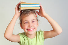 Smiling little girl hold books. On head Stock Image