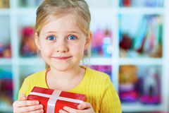 Smiling little girl hold red gift against her room Stock Photos
