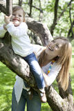 Smiling little girl hold for tree Stock Photo