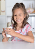 Little girl holding cup of tea Stock Images