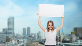 Smiling little girl holding blank white board Royalty Free Stock Photo