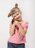 Smiling little girl holding a doll. In a studio Royalty Free Stock Images