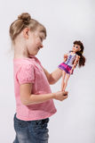 Smiling little girl holding a doll. In a studio Stock Photo