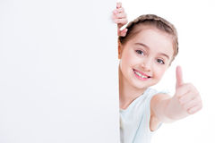 Smiling little girl holding empty white banner. Royalty Free Stock Images