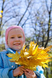 Smiling little girl holding fall leaves Stock Photo