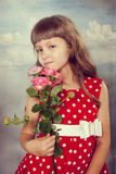 Smiling little girl holding flowers. Closeup. Photo in retro style with old textured paper Stock Image