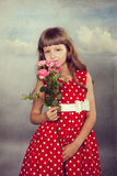 Smiling little girl holding flowers. Closeup. Photo in retro style with old textured paper Royalty Free Stock Image