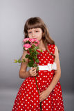 Smiling little girl holding flowers. On gray background Royalty Free Stock Photography