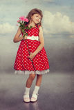 Smiling little girl holding flowers. Photo in retro style with old textured paper Stock Photos