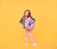 Smiling little girl holding a giant donut pillow Royalty Free Stock Photo