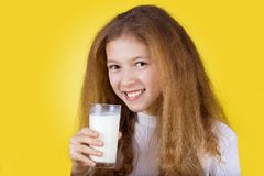 Smiling Little girl holding a glass of milk over yellow background. royalty free stock photography