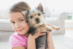 Smiling little girl holding her yorkshire terrier puppy Royalty Free Stock Photo