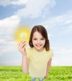 Smiling little girl holding light bulb Stock Photos