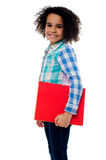 Smiling little girl holding a notebook Royalty Free Stock Photography