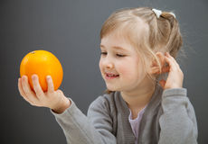 Smiling little girl holding an orange Royalty Free Stock Image