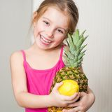 Little girl with a pineapple and lemon Royalty Free Stock Image