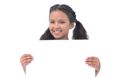 Smiling little girl holding and presenting sign at camera Royalty Free Stock Images