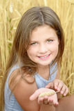 A smiling little girl holding rye spike on hand. Golden rye field at summer day. Concept of purity, growth, happiness royalty free stock photo