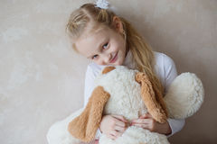 Smiling little girl holding a toy dog Royalty Free Stock Image