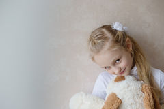 Smiling little girl holding a toy dog Royalty Free Stock Images