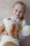 Smiling little girl holding a toy dog Stock Photos