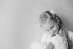 Smiling little girl holding a toy dog Royalty Free Stock Photography