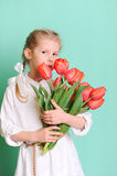 Smiling little girl holding tulips. Portrait of smiling cute kid girl holding red tulips on blue background in studio Royalty Free Stock Photo