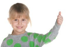 Smiling little girl holds her thumb up Royalty Free Stock Images