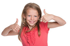Smiling little girl holds her thumbs up Royalty Free Stock Photos