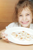 Smiling little girl holds plate with cookies Royalty Free Stock Image